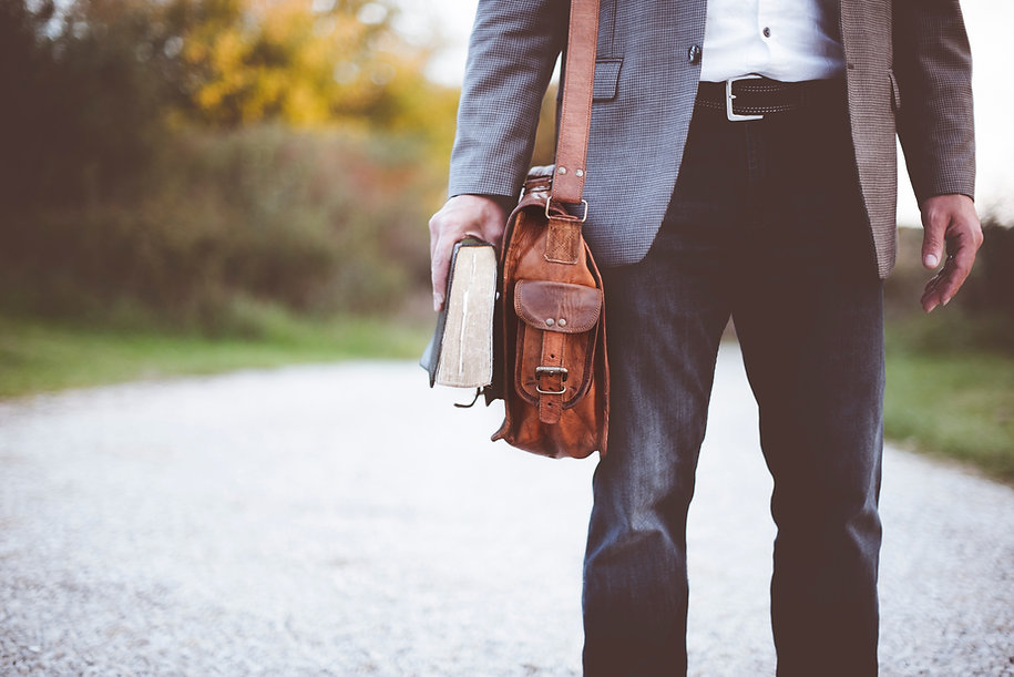 Image by Ben White of man in jeans with leather satchel and book