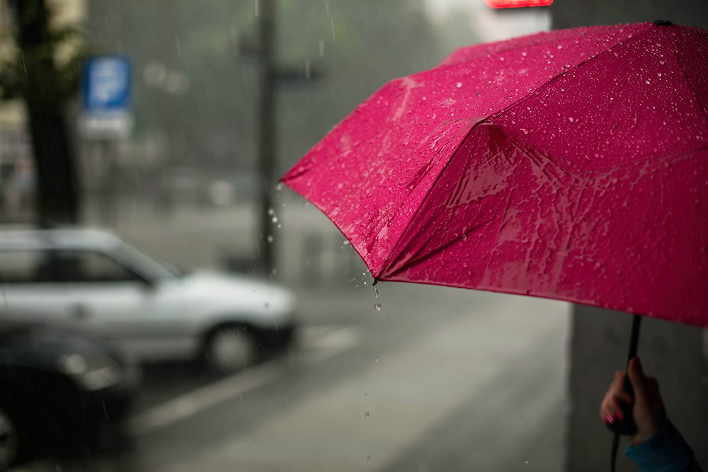 Person standing in the rain under a red umbrella