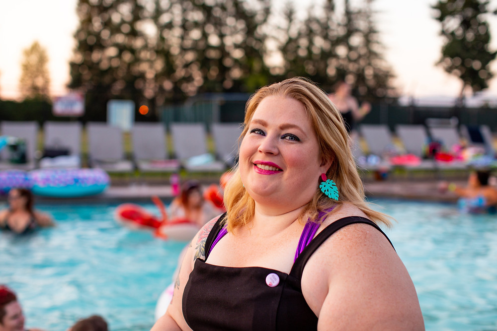 a blond female in a larger body next to a pool, wearing a black strappy top and turquoise earrings and smiling into the camera
