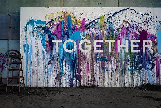 Image by Adi Goldstein seinämaalaus, jossa lukee together.