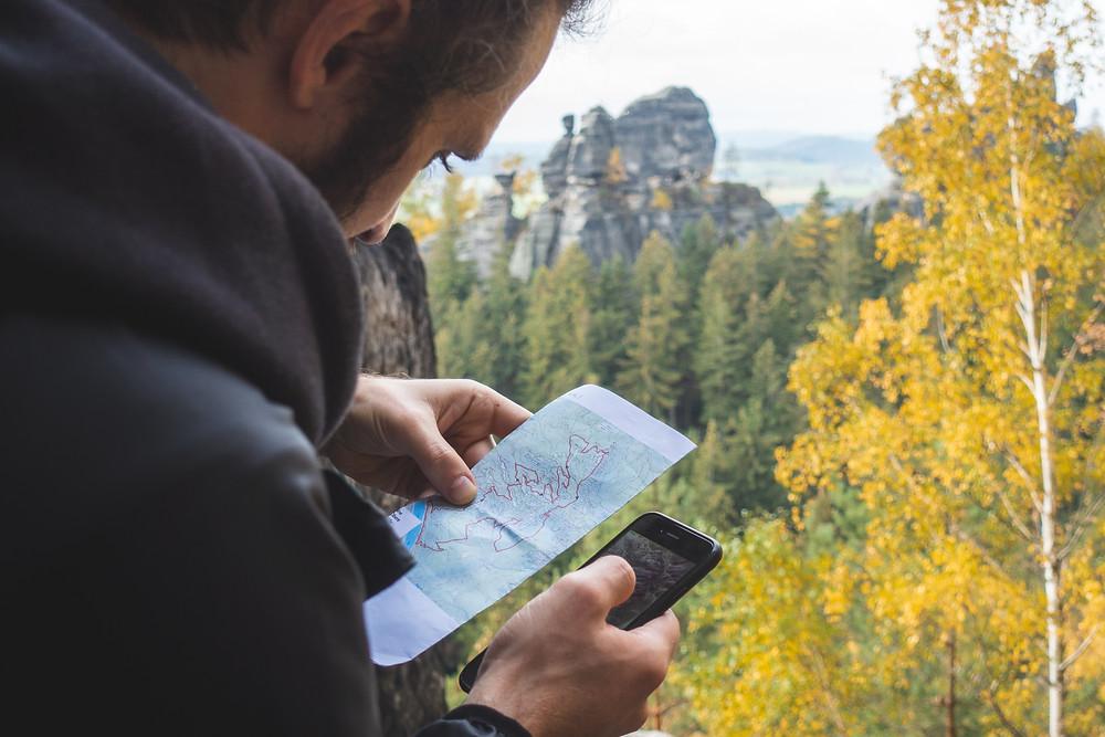 Mann blickt auf Wanderkarte und Smartphone.