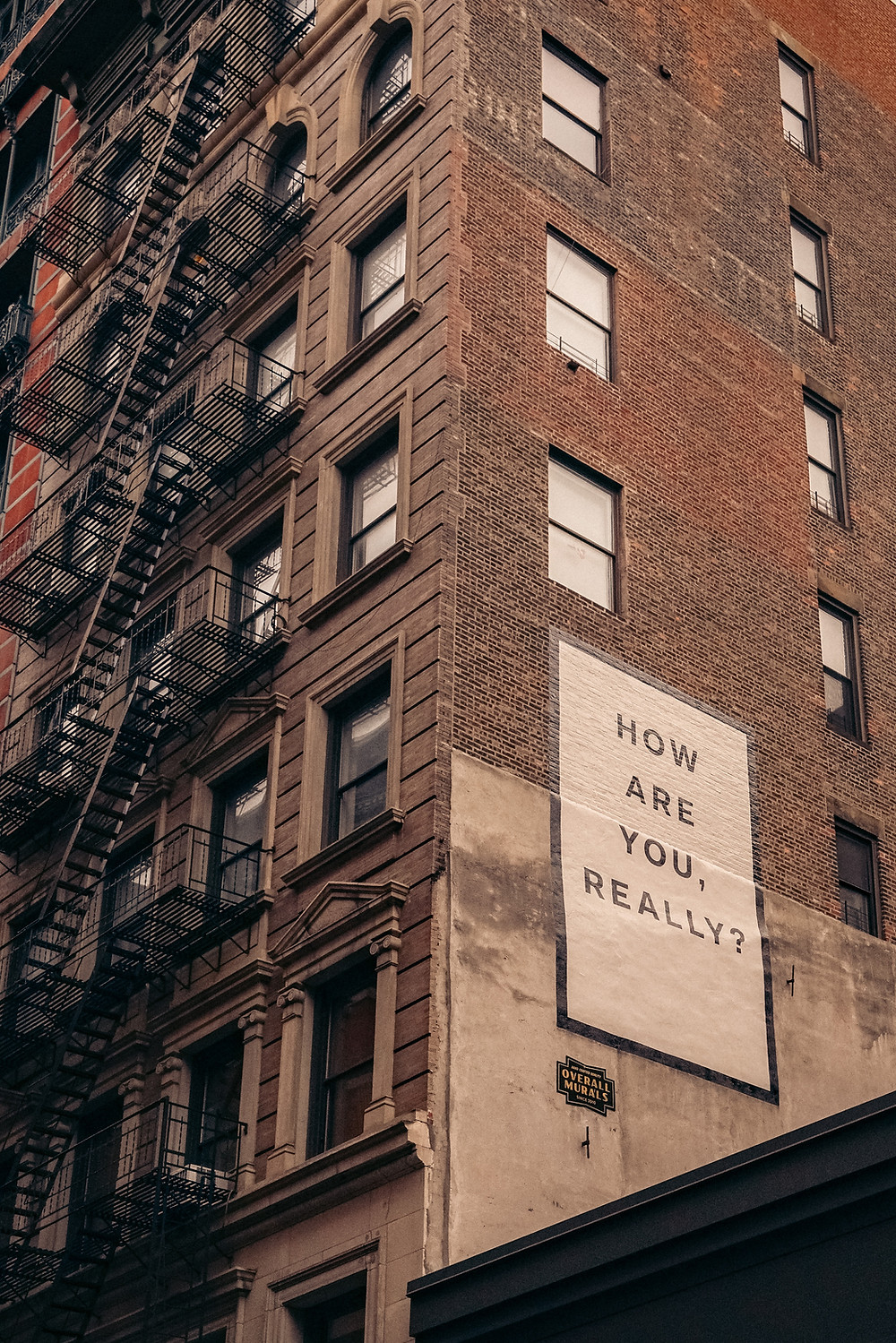"""An apartment building with a sign on the side that says, """"How are you really?"""""""