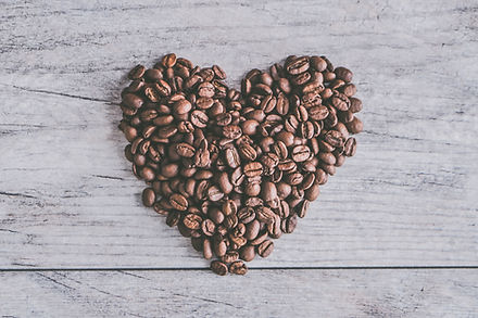 Coffee beans shaped in a heart on wood table