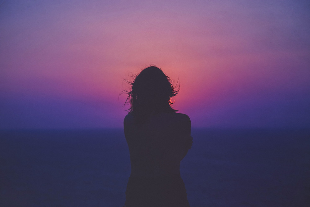 A silhouette of a woman standing in front of a sunset.