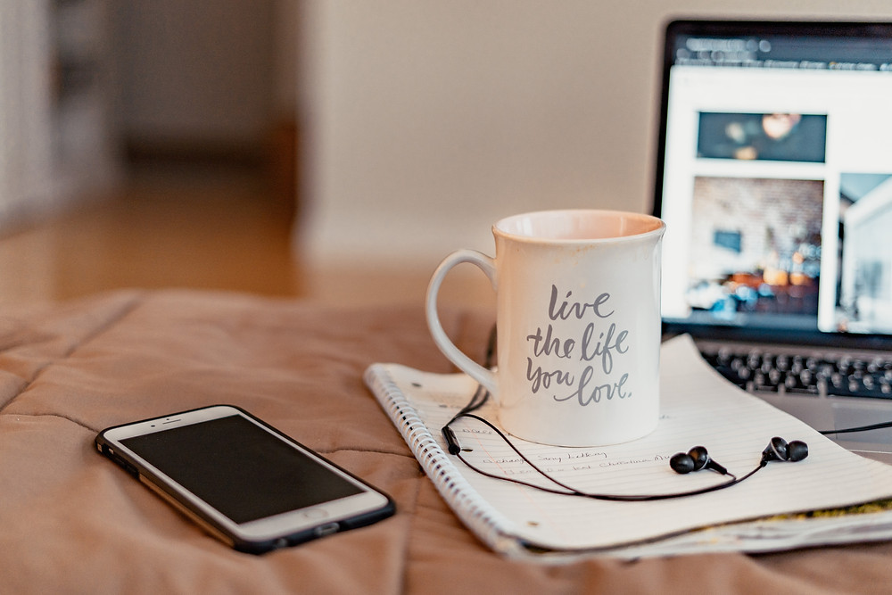 a coffee mug, laptop and cell phone on a bed
