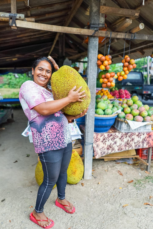 woman holding large jackfruit
