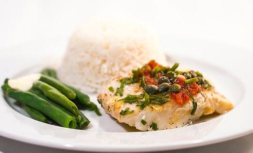 Un morceau de poisson accompagné de capres, herbes, tomates et de légumes verts. Il y a une portion de riz en arrière-plan
