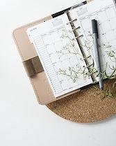 Kalender und Stift mit etwas Grüner Dekoration