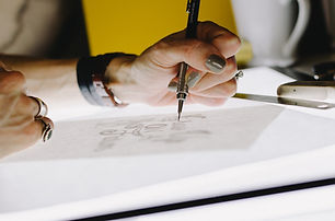 A woman's hand designing a company logo on a piece of paper