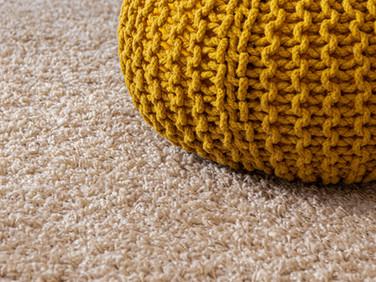 Knit pouf on a clean tan carpet.