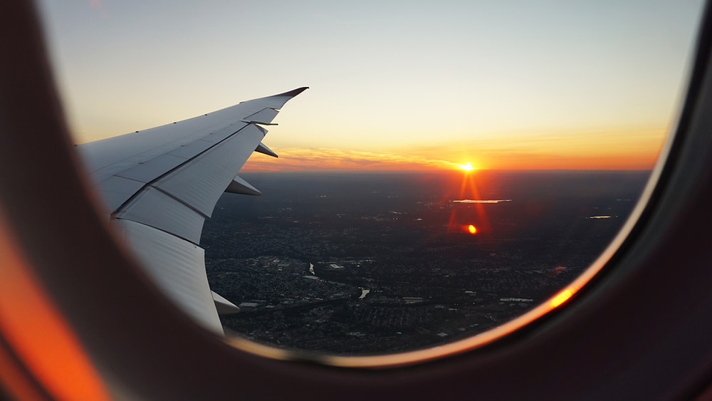 A sunset over the horizon line.  The wing of an airplane and the shot from the airplane window.