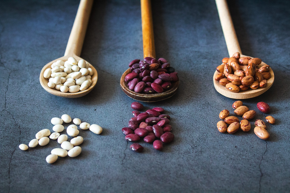 dried beans on a table and in spoons