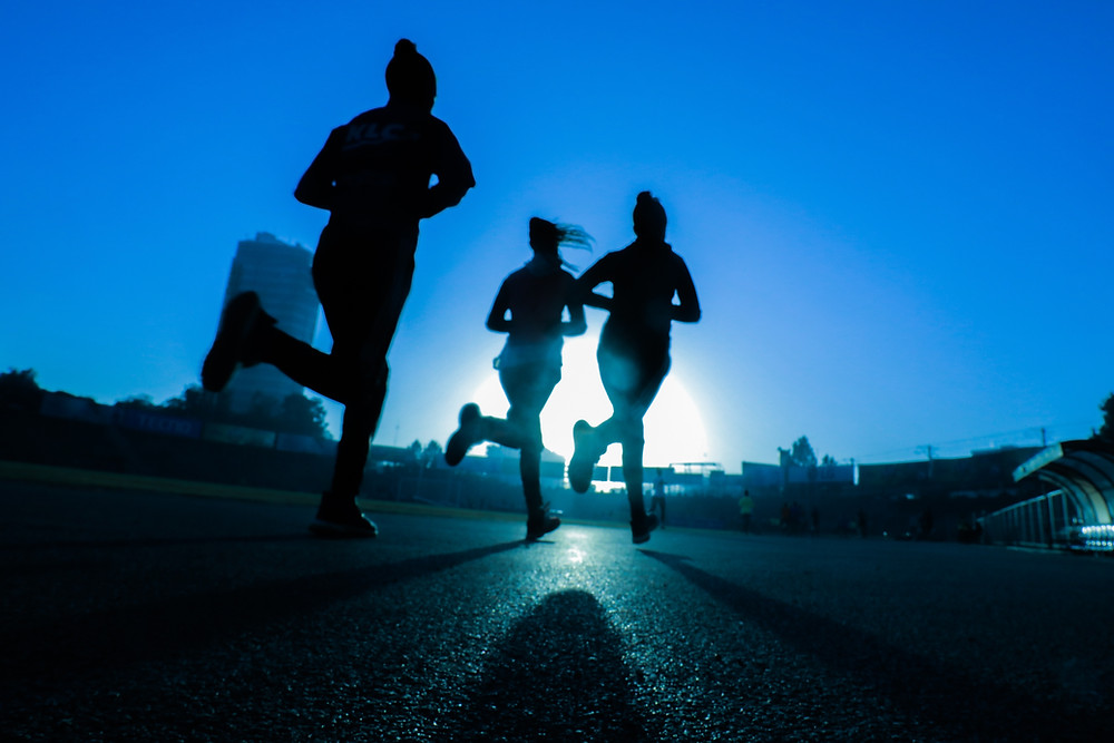 Silhouette of 3 women runners on track with clear skies