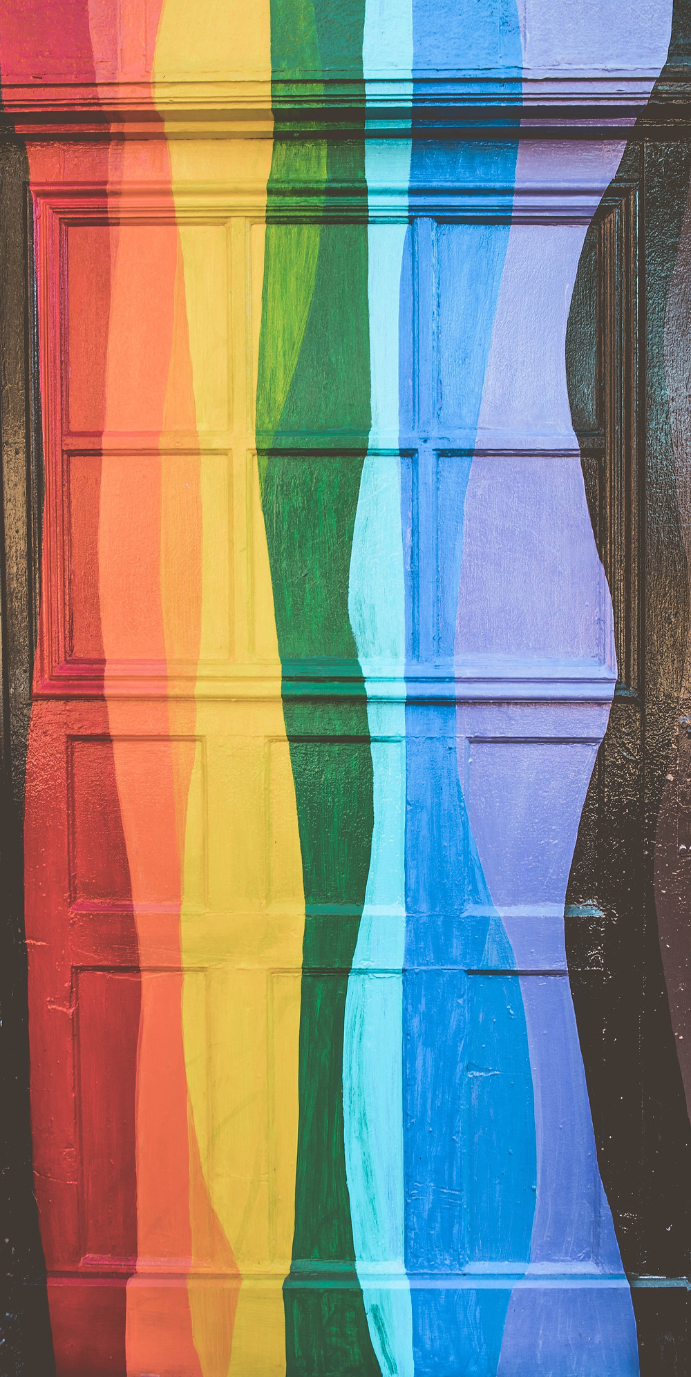 Front door painted in rainbow Pride colours.