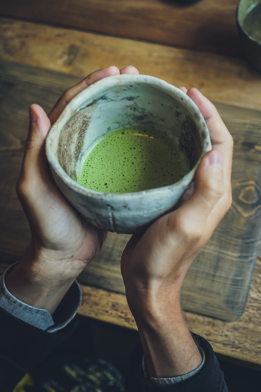 a warm matcha latte in a tea cup being held by two hands