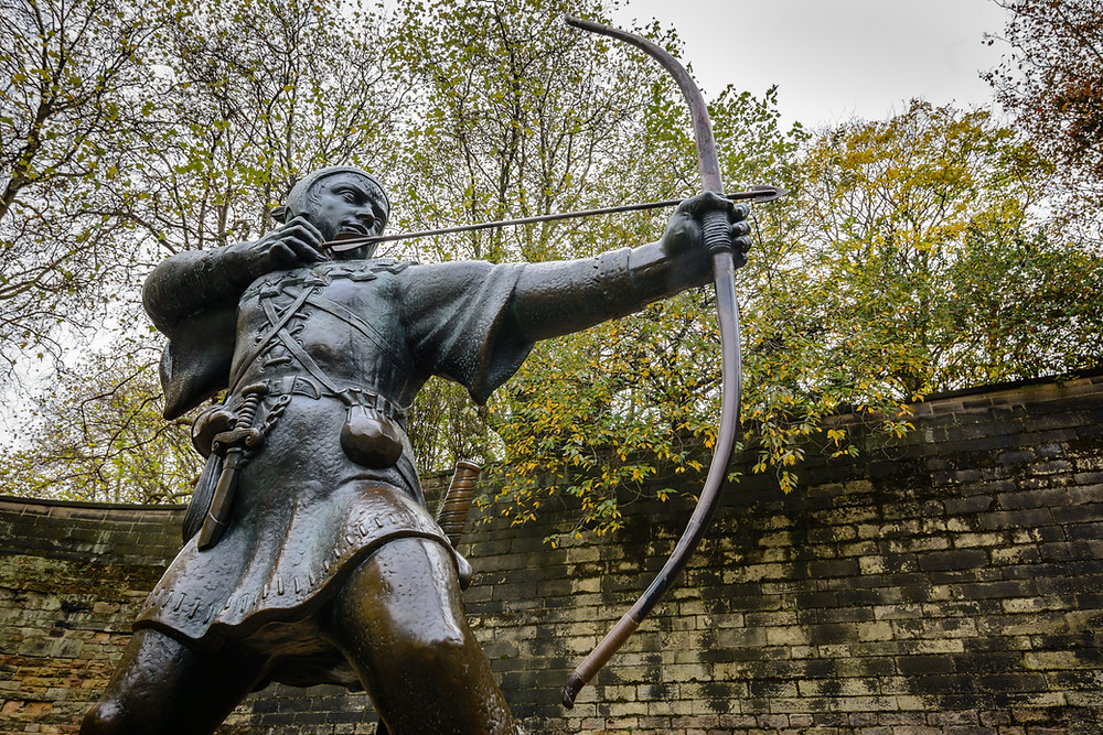 bronze statue of robin hood holding bow and arrow