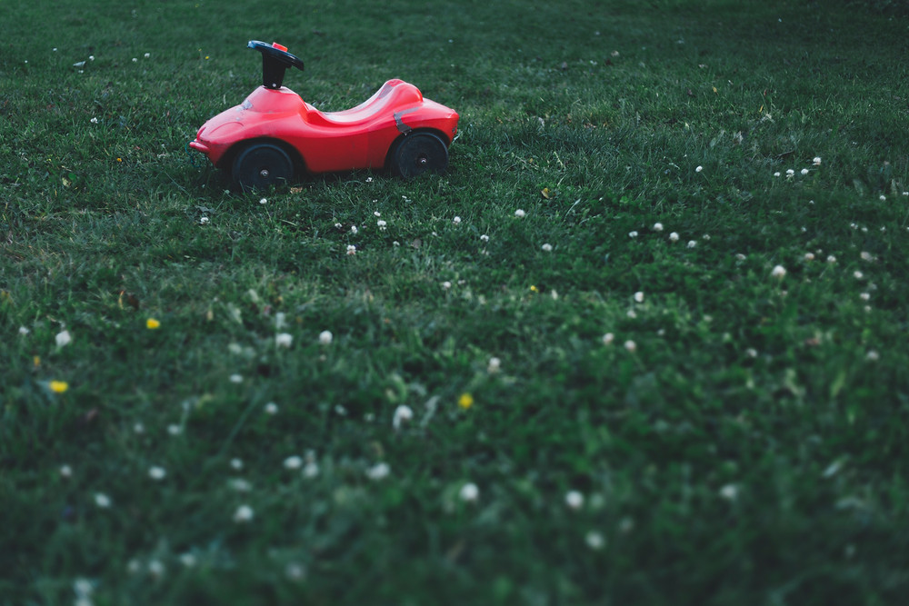 A child's scooter sits empty on the lawn.