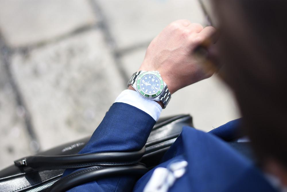 ผู้ชายนักธุรกิจยกมือข้างซ้ายขึ้นดูนาฬิกา