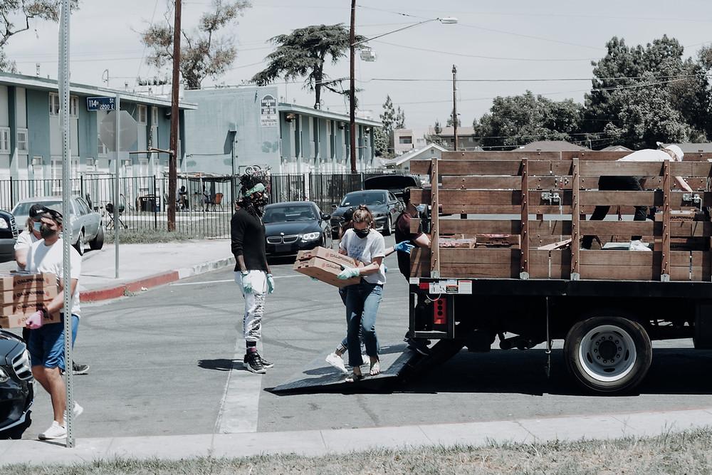 Pessoas entregando doações durante a pandemia do coronavírus. Elas estão descarregando caixas de um caminhão em meio a uma via