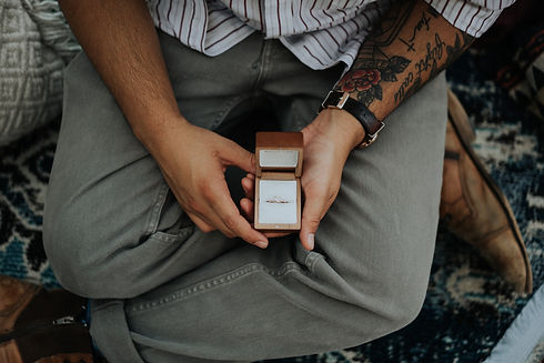 Image of man holding an engagement ring | Photo by George Coletrain