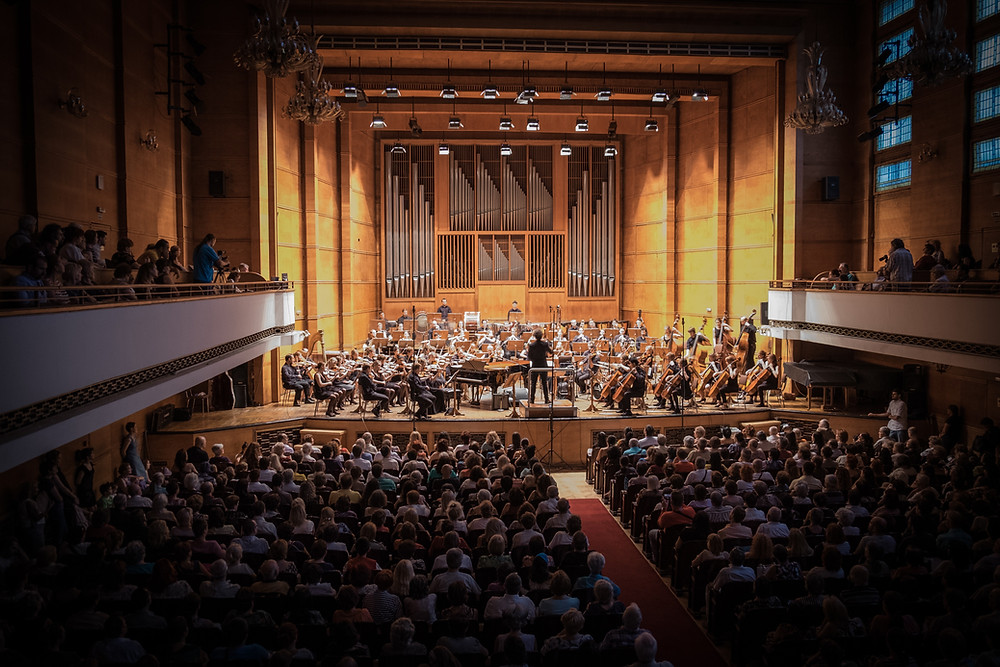 Orchestra in hall with audience and conductor