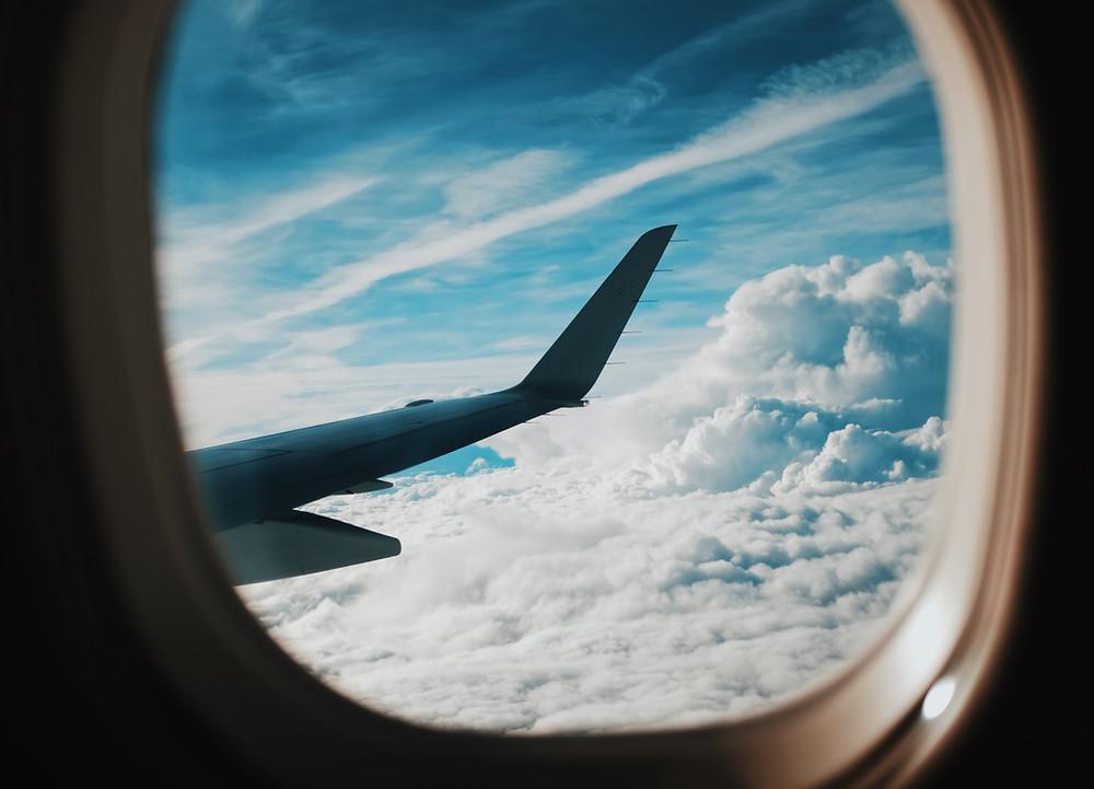 Janela do aviao com vista para asa e nuvens