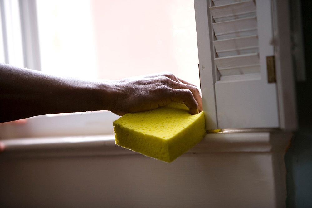 Sponge being used to clean a window sill