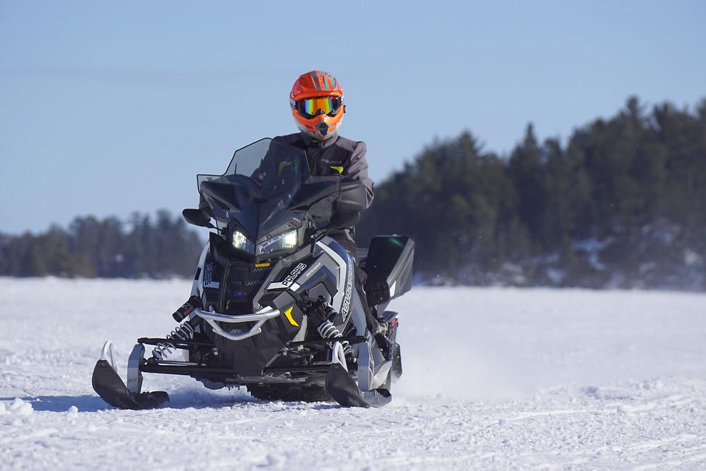 man snowmobiling on snow