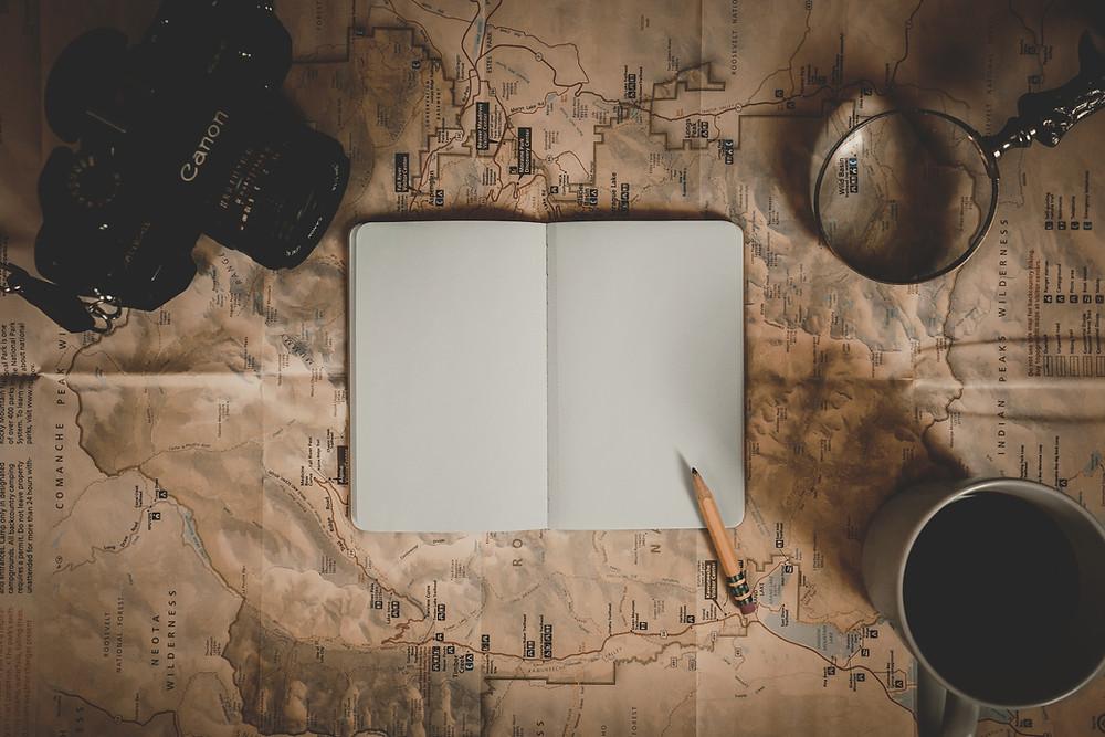 un cuaderno y un lápiz sobre un mapa