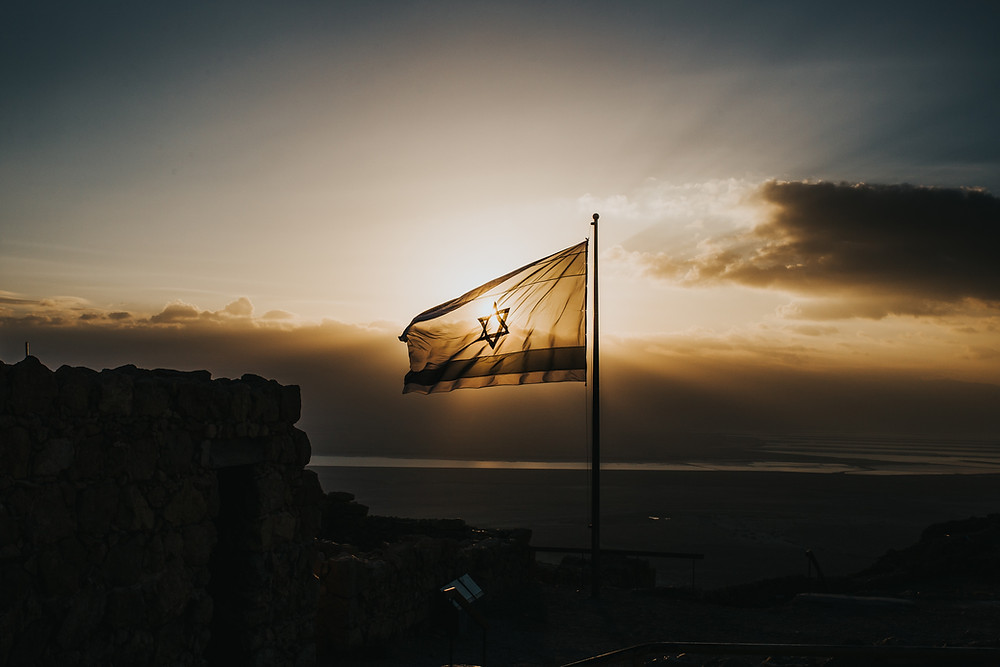 An Israeli flag ontop of a mountain with the sunset behind