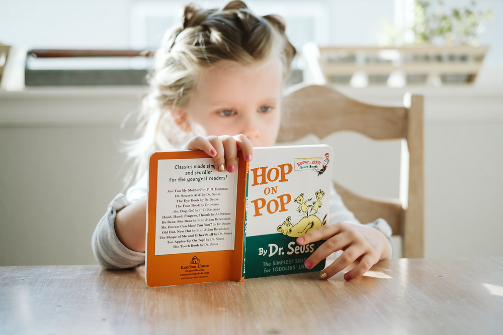 little girl reading a dr seuss book at the kitchen table