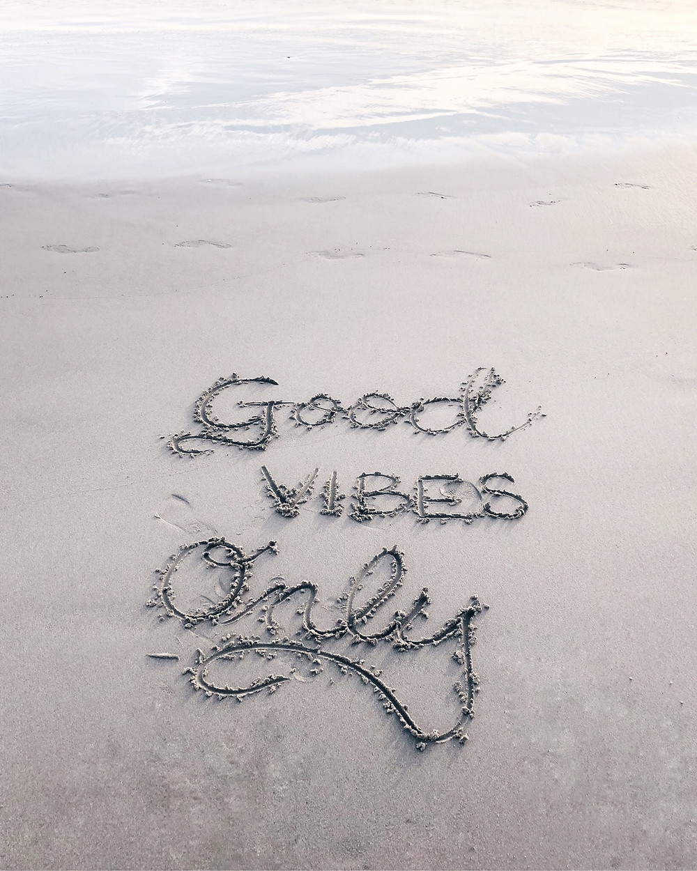 """Message written in the sand by the water that says """"good vibes only."""""""