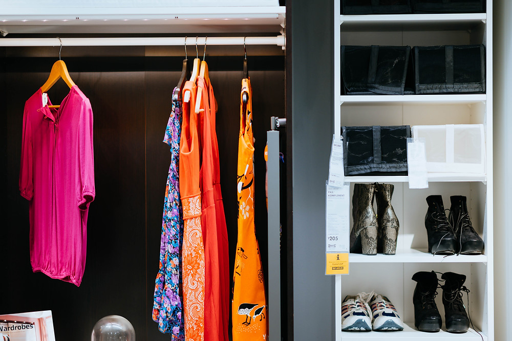 clothes hanging in a wardrobe with shoe storage