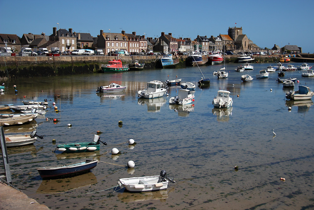 the harbour of Barfleur in Normandy, France with small boats, quayside houses and Saint-Nicolas church and a Normandy blue sky
