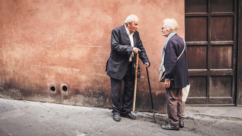 senhor e senhora conversando na rua