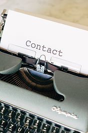 "An old-fashioned typewriter with a white sheet of paper with the word ""Contact"" written on it."
