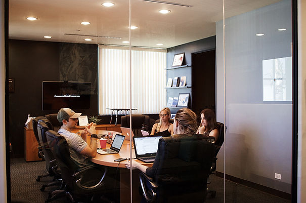 A group of adults with laptops discussing at a around table in an office room.