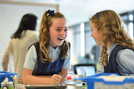 Two girls in school uniform happily chatting in the classroom