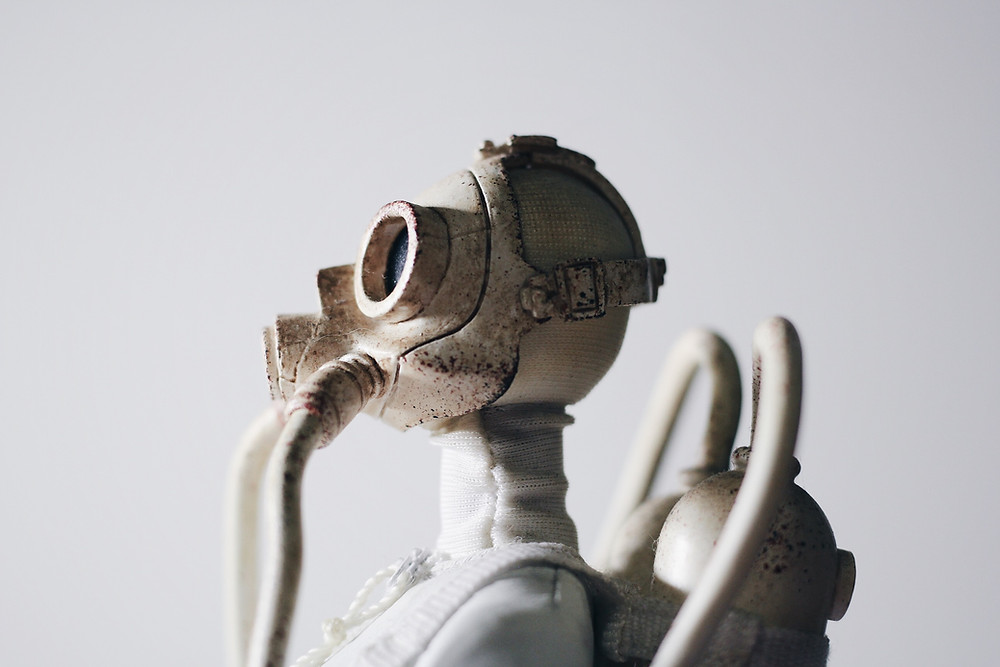 White figurine wearing a gas mask with oxygen tank