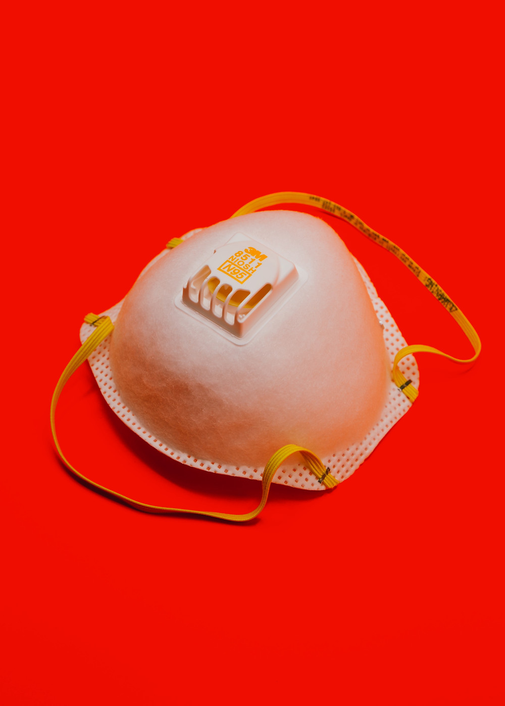 A single N-95 mask on a red background.