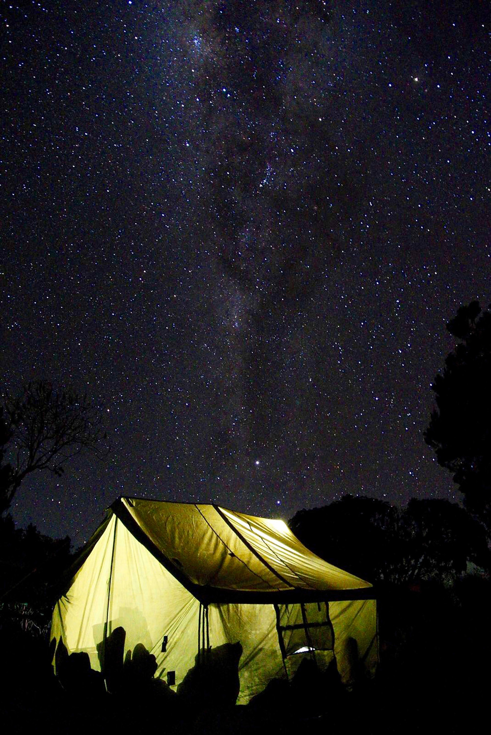 Large, yellow-green, pentagon-shaped, group tent under the milky way and dark night skies in Gatlinburg, Tennessee