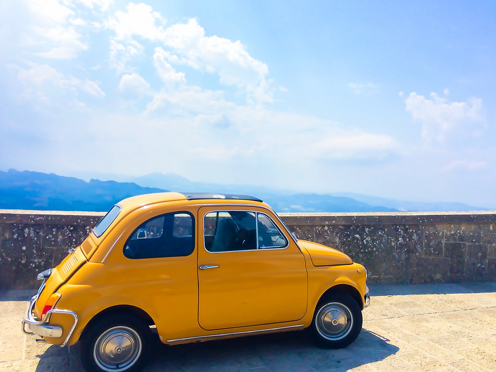 bright yellow old Fiat car parked at a mountain overlook on a sunny day