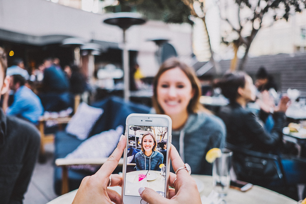 Zillennial's are a real micro-generation; friend takes a picture of woman at restaurant