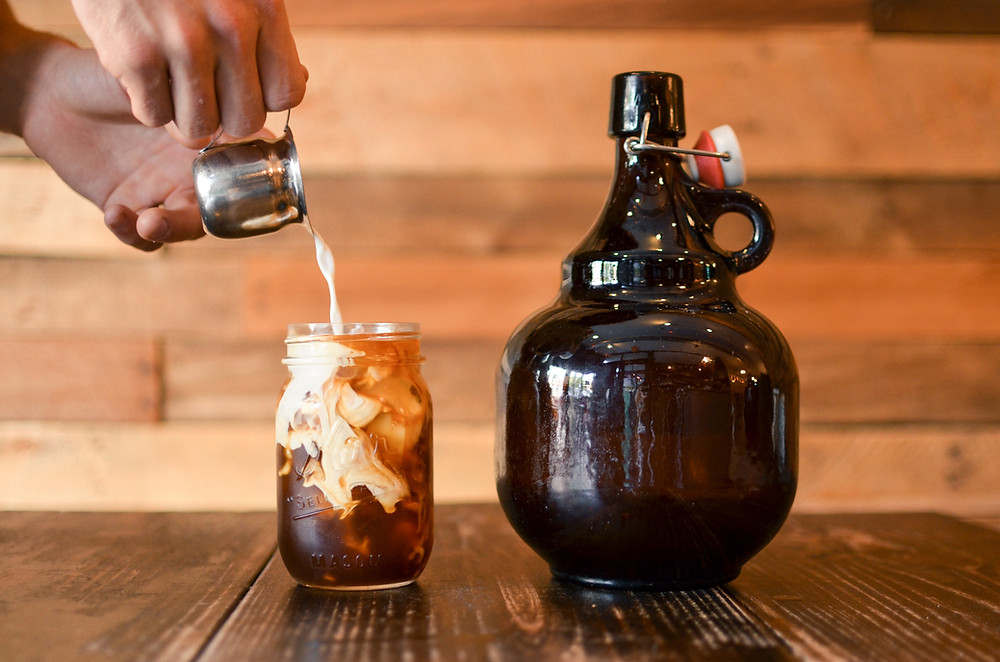 Person pouring milk into glass with cold brew coffee beside an amber jug.