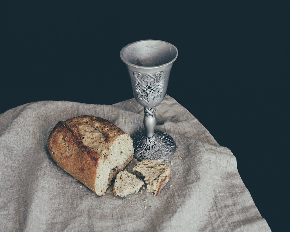Bread loaf and wine cup in preparation for communion.