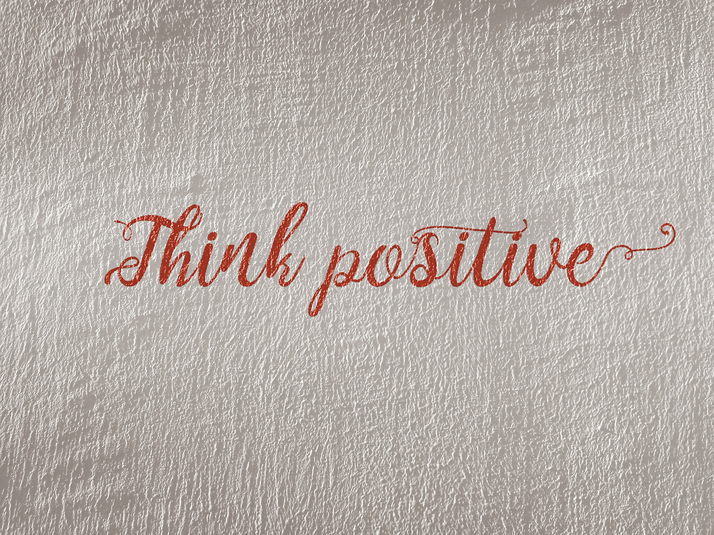 red words in cursive that read Think Positive on white linen fabric