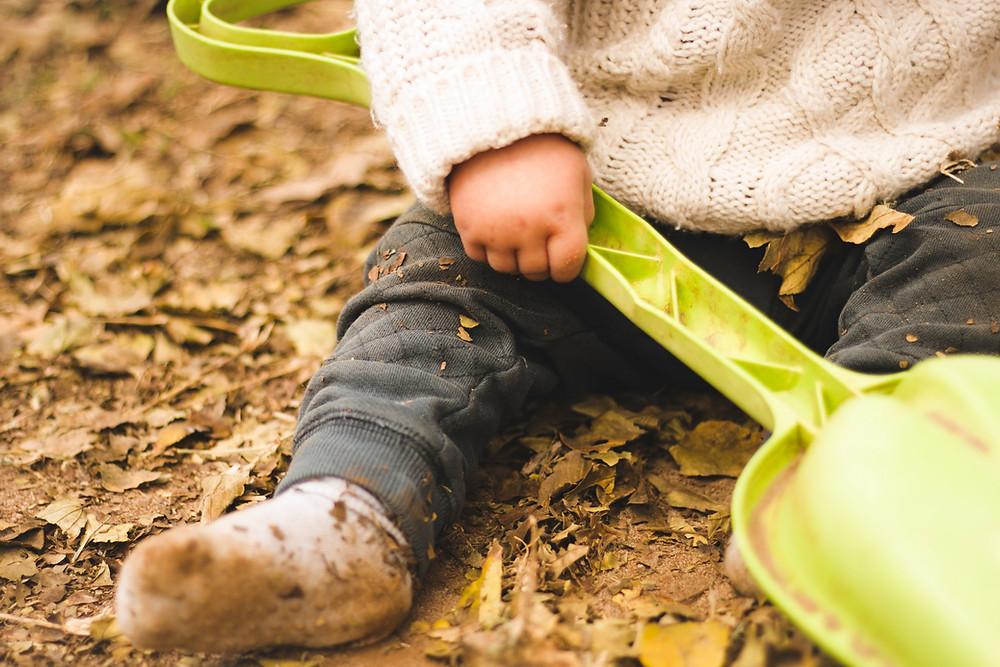 Baby holding a plastic shovel