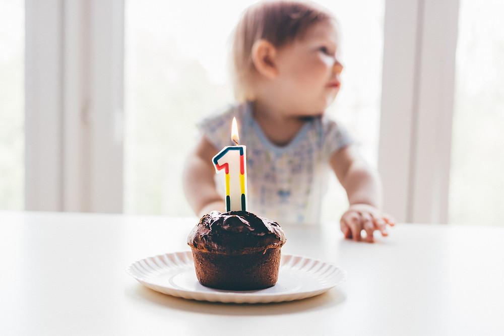 Bebe olha para o lado enquanto a sua frente está um cupcake com uma vela acesa de 1 ano.