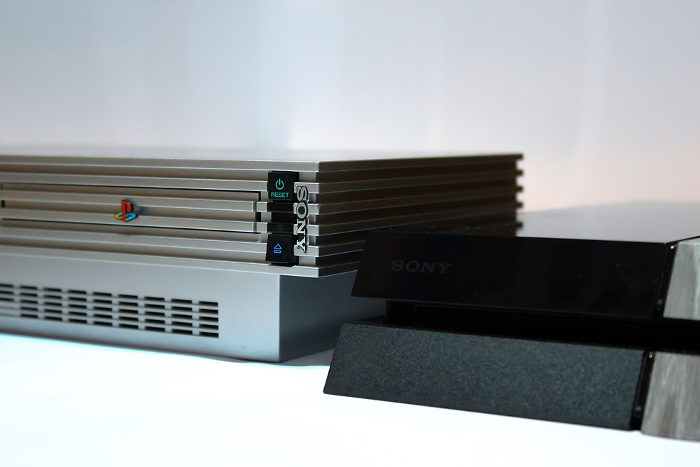 A Playstation 2 and 4 standing side by side.