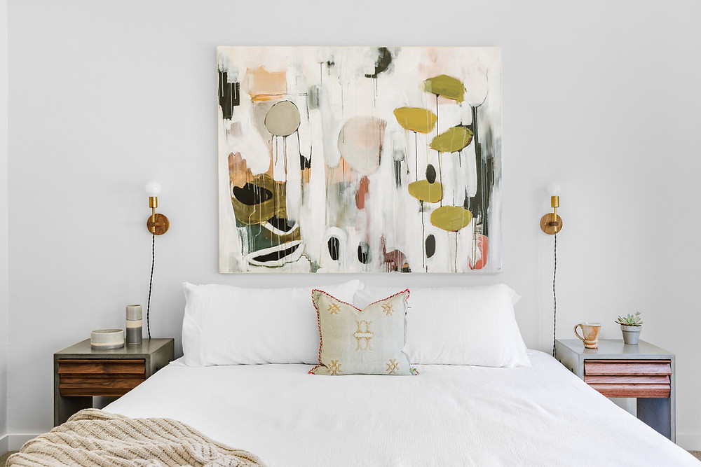 Soft colors behind the bed give calmness and elegance